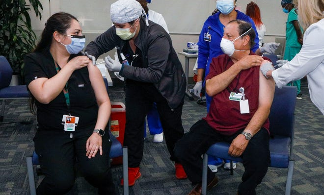 Dr. Steven Rosenberg, of Palm Beach Dermatology, and his daughter Dr. Miranda Rosenberg, a senior resident in the University of Miami dermatology department, receive the COVID-19 vaccination together at Jackson Memorial Hospital's Ira C. Clark Diagnostic Treatment Center in Miami on Friday.