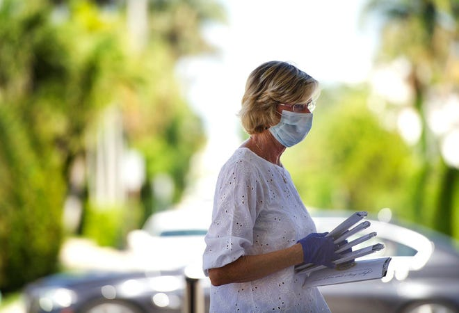 A mask-wearing Mayor Gail Coniglio helps the Palm Beach Police and Fire Foundation distributed 20,000 masks to residents in May at St. Edward Catholic Church.