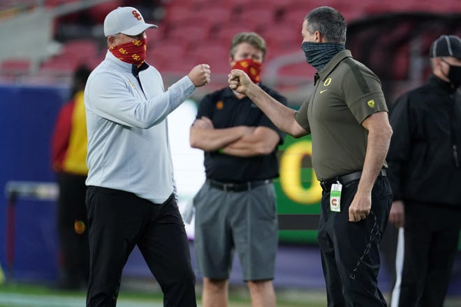 outhern California Trojans head coach Clay Helton and Oregon Ducks head coach Mario Cristobal bump fists before the Pac-12 Championship at United Airlines Field at Los Angeles Memorial Coliseum on Dec. 18, 2020.