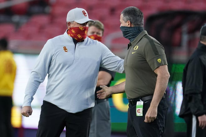 USC coach Clay Helton, left, greets Oregon coach Mario Cristobal prior to Friday's Pac-12 championship game.