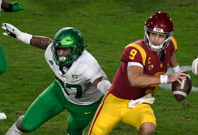 Oregon defensive tackle Brandon Dorlus flushes USC quarterback Kedon Slovis out of the pocket during the first quarter of Friday's Pac-12 championship game. Dorlus had three tackles, a quarterback sack and a pass break up in the game.