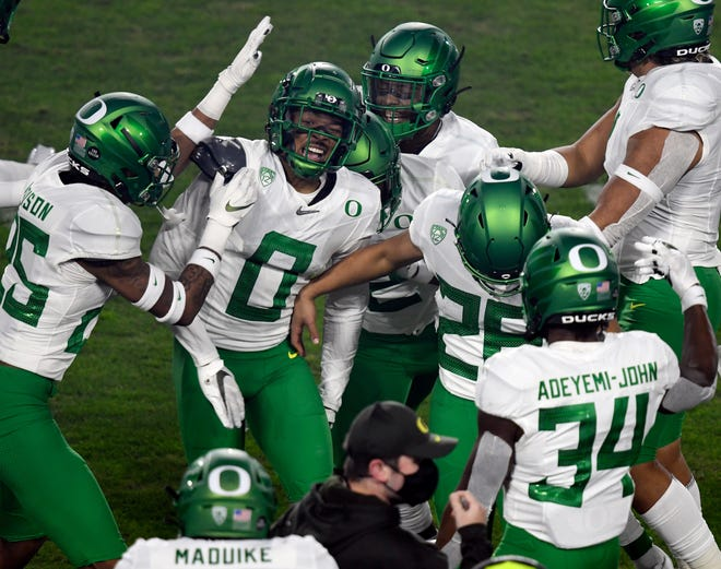 Oregon cornerback Deommodore Lenoir (0) celebrates his first-quarter interception with teammates during the Ducks' 31-24 Pac-12 championship game win over USC on Friday in Los Angeles.