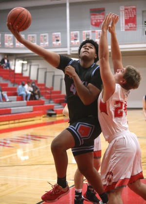Stephen Gales (left) of Alliance takes a shot while being guarded by Tyler Pritchard of Canton Sourth during their game at Canton South on Friday, Dec. 18, 2020.
