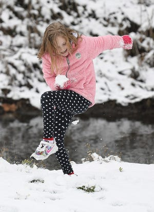 Nine-year-old Isabelle Barker moves carefully through the snow at Reservoir Park in Massillon in December while having a snowball fight with her friend Lucia Hererra.