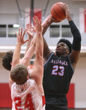 Alliance's Brandon Alexander (23) takes a shot while being guarded by Canton South's Tyler Pritchard (24) during Friday's game. (CantonRep.com / Scott Heckel)