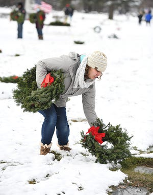 Maria Phillips lays a wreath at a veteran's grave at Calvary cemetery Saturday. The Perry Rotary Club laid wreaths on the graves of veterans buried in the cemetery as part of Wreaths Across America, a coordinated effort across the United States and abroad to honor veterans during the holiday season.