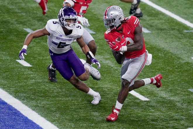 Ohio State running back Trey Sermon, right, scores past Northwestern defensive back JR Pace (5) during the second half of the Big Ten championship game, Saturday in Indianapolis.