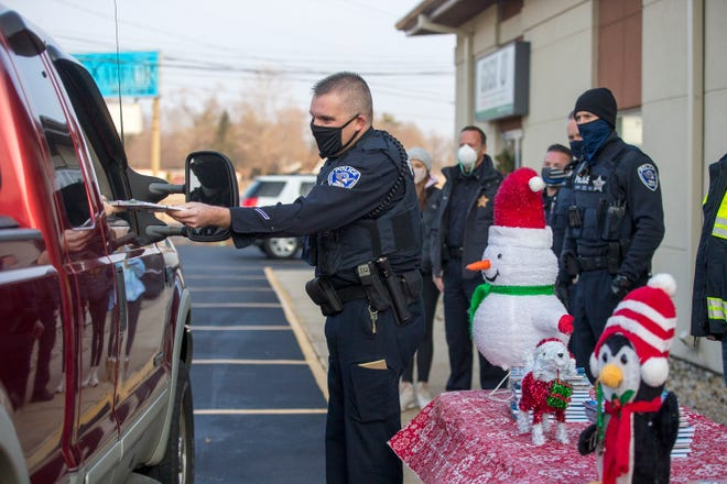 "GiGi's Playhouse employees and officers from the Rockford Police Department greet kids and hand out small gifts at GiGi's on Saturday, Dec. 19, 2020, in Machesney Park. GiGi's Playhouse Rockford serves about 375 individuals with Down syndrome and their families across a five-county area. Due to the coronavirus pandemic shutdown this event replaced the organization's annual ""Holidays and Heroes"" event in which 30 participants from the Playhouse go shopping with a police officer."