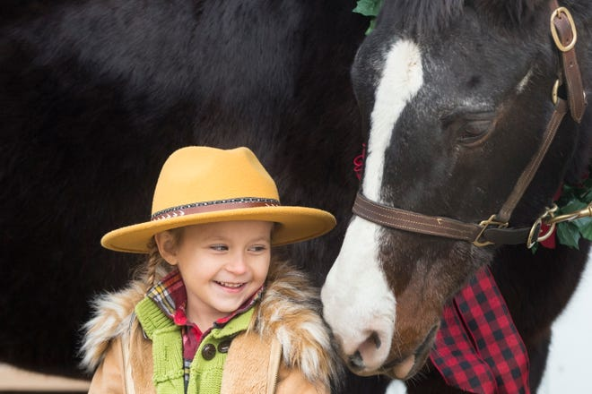 Birdie Lanier, 5, of Rockford, meets Ben, the Arabian horse, and poses for pictures during the Holiday Horse event at Lockwood Park Equestrian Center on Saturday, Dec. 19, 2020, in Rockford.