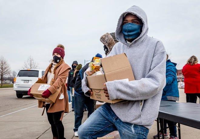 """Djay Harris balances a box of food as he waits for the next car to pull up as volunteers distribute food to anyone in need during a food distribution by the Central Illinois Foodbank with food provided by Dot Foods Inc. on West Lafayette Avenue, Friday, December 18, 2020, in Jacksonville, Ill. """"It makes me feel good inside,"""" said Harris. """"I know a lot of the families are in need. It makes me want to help the community out and that I'm doing a good deed."""" [Justin L. Fowler/The State Journal-Register]"""