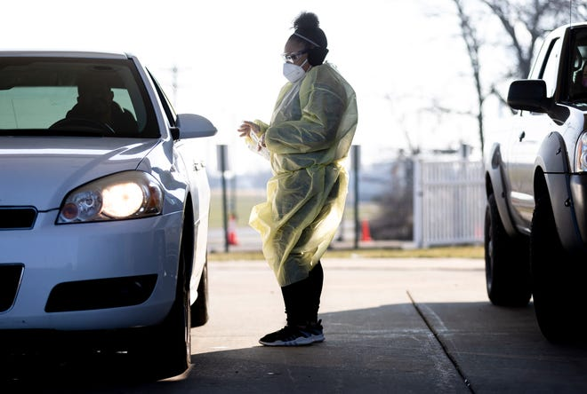 With a cold wind whipping her paper gown around, Jayla White, 21, a member of SIU Medicine's COVID-19 response team, prepares to conduct COVID-19 tests on Dec. 17 during SIU Medicine's mobile testing site at Abundant Faith Christian Center in Springfield. [Justin L. Fowler/The State Journal-Register]