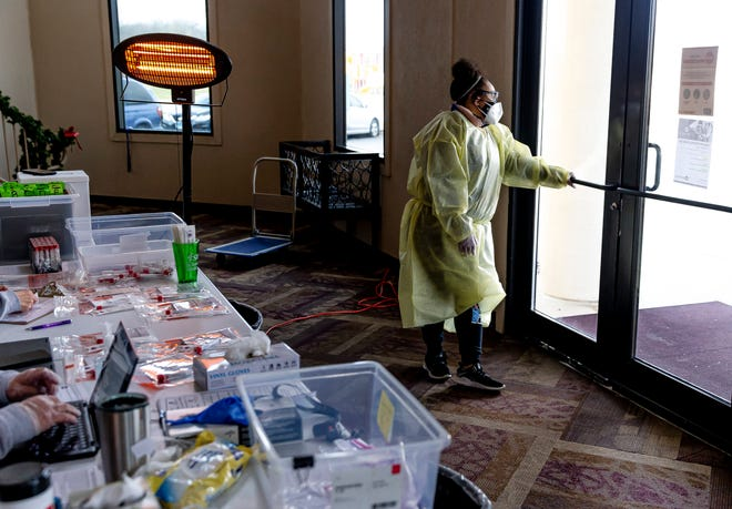 With a space heater buzzing to the left, Jayla White, 21, a senior at Southern Illinois University Edwardsville majoring in social work and a member of SIU Medicine's COVID-19 response team, pauses for a moment draped in personal protection equipment as she prepares to conduct another COVID-19 test during SIU Medicine's mobile testing site at Abundant Faith Christian Center on Dec. 17 in Springfield. [Justin L. Fowler/The State Journal-Register]