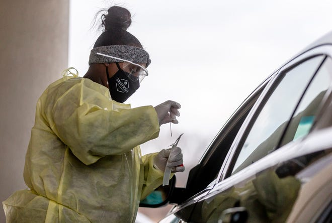 Diamond Dodson, a member of SIU Medicine's COVID-19 response team, collects a sample at its mobile testing site at Abundant Faith Christian Center and secures it in a vial to be tested. [Justin L. Fowler/The State Journal-Register]