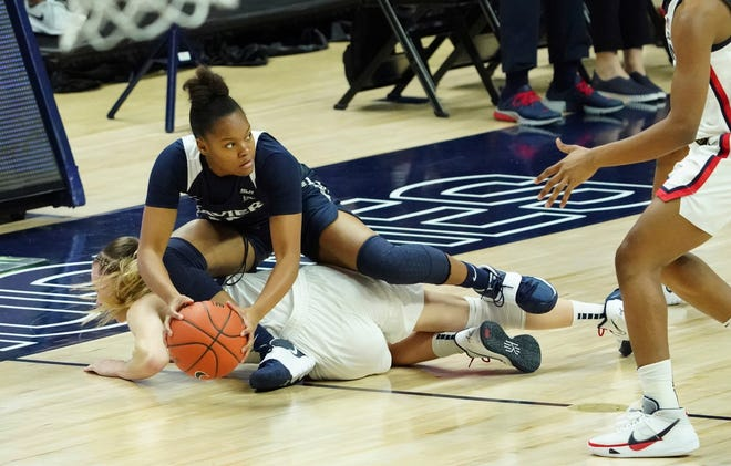 Xavier guard Mackayla Scarlett (15) works for the ball on top of Connecticut guard Paige Bueckers (5) during the first half of an NCAA college basketball game, Saturday, Dec. 19, 2020, in Storrs [David Butler II/Pool Photo via AP]