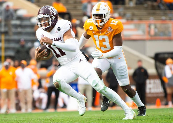 Texas A&M quarterback Kellen Mond scrambles with Tennessee linebacker Deandre Johnson in pursuit Saturday in Knoxville, Tennessee.