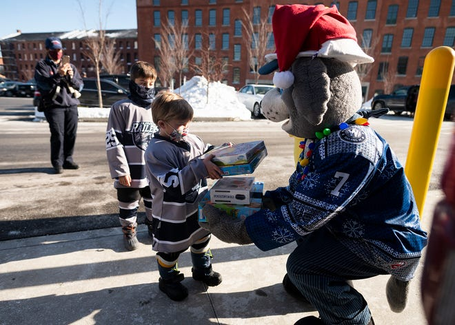 WORCESTER - Noah, 5, and Ethan Lavallee, 8, hand off toy donations to Trax during the Railers' Teddy Bear Toss & Toy Drive to benefit the Friendly House of Worcester on Saturday.