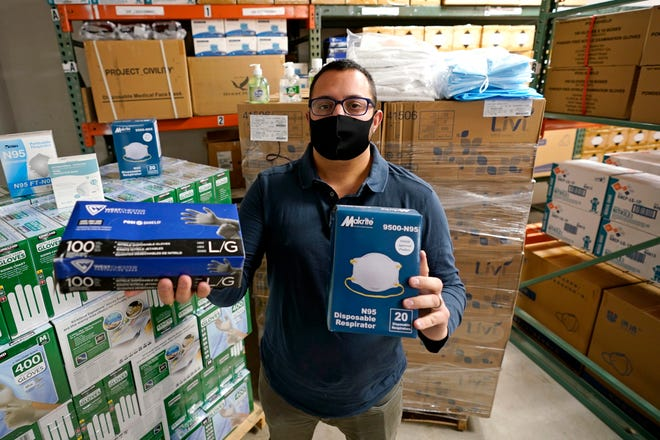 Ray Bellia holds up personal protective masks and gloves, used by medical and law enforcement professionals, in the warehouse of his Body Armor Outlet store Dec. 9 in Salem, N.H.