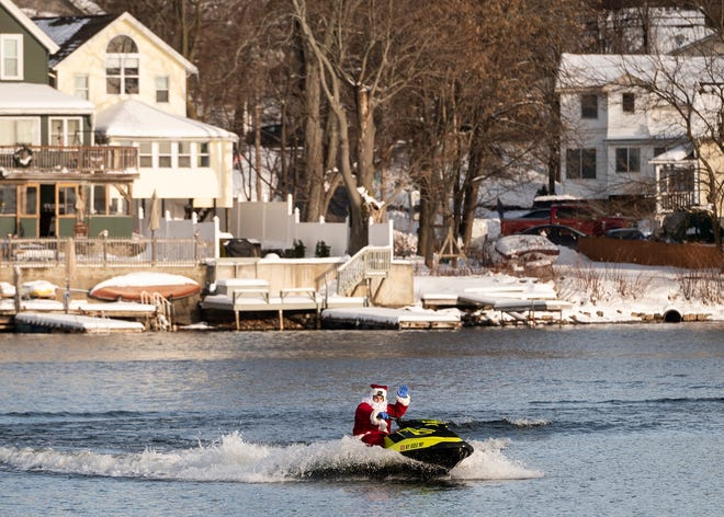 WORCESTER - Santa Claus, a good friend of John Sullivan, passes by on his jet ski on Lake Quinsigamond for the first annual Santa Wet Run on Saturday, December 19, 2020.