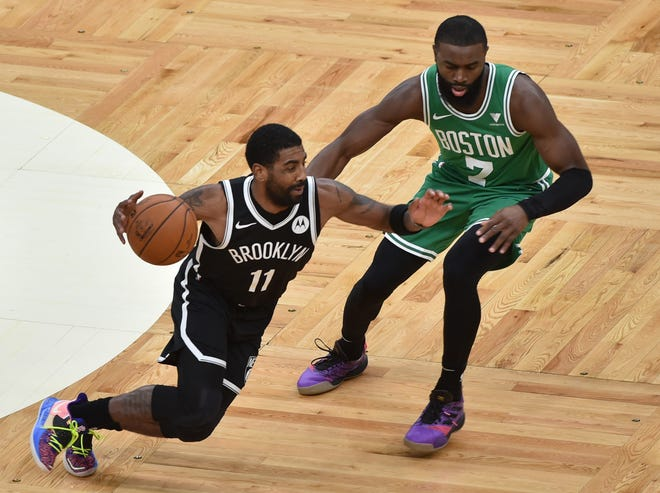 Nets guard Kyrie Irving brings ball upcourt, with Celtics guard Jaylen Brown defending during the first half of a preseason game Friday night.