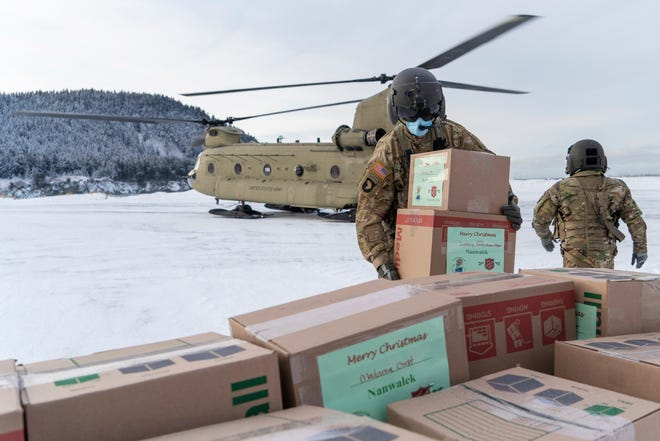 In this photo provided by the Alaska National Guard, soldiers from 1st Battalion, 207th Aviation Regiment, unload gifts from a CH-47 Chinook helicopter Dec. 11 in Nanwalek, Alaska, during Operation Santa Claus.