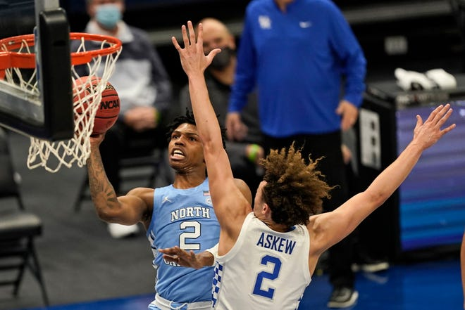 North Carolina's Caleb Love, left, floats to the basket past Kentucky's Devin Askew during Saturday's game in Cleveland.