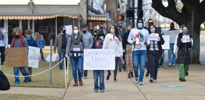 Concerned citizens march around the Tuscaloosa County Courthouse and adjacent Tuscaloosa County Sheriff's Office on Saturday, Dec. 2020. The group is demanding that the Sheriff's Office releases information and data concerning COVID-19 in the county jail.