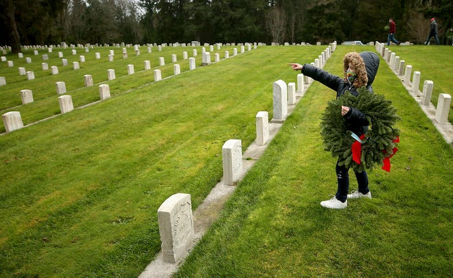 With a wreath in hand Meeah Lucas, 7, of Port Orchard, points out the section of the cemetery that she's heading for to her grandmother Tara as they take part in the Wreaths Across America event at Washington Veterans Home Cemetery in Port Orchard on Saturday.