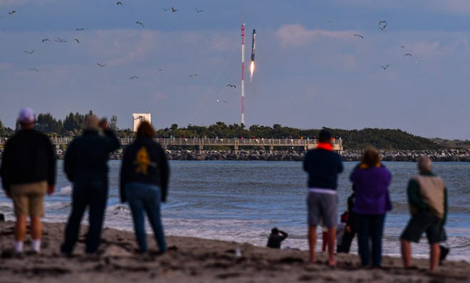 People on the beach in Cape Canaveral watch the booster landing at Cape Canaveral Space Force Station. SpaceX launched a Falcon 9 rocket from Pad 39A at Kennedy Space Center on Saturday, Dec. 19, 2020, on a mission for the National Reconnaissance Office.