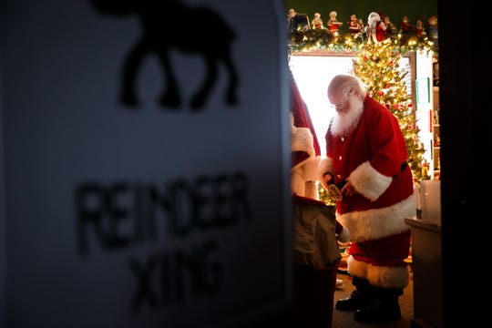 """In his office known as the """"Santa room,"""" Dave Greulich, 68, gets ready to go outside and hear kids' Christmas wishes as Santa Claus on Dec. 15, 2020, in Ames, Iowa. For the past seven years, Greulich has turned his front yard into a Christmas wonderland for families to visit Santa."""