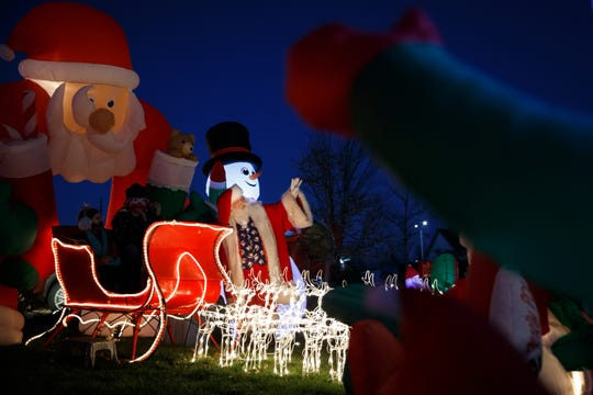 """Dave Greulich, 68 of Ames, Iowa, also known as Santa, waves as a parent takes a photo on Nov. 28, 2020. What started as a way to make some extra money has turned into a vocation for Greulich, """"I am Santa 24/7,"""" he said."""