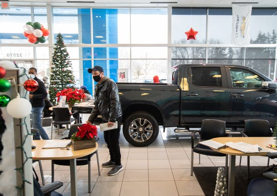 A customer talks with a salesman in the showroom of Feldman Chevrolet of Livonia on December 18, 2020.