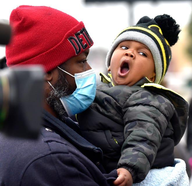 Elijah Jackson, 11 bulan, beristirahat di pelukan ayahnya, Melvin Jackson, keduanya dari Detroit, sebelum mereka menerima hadiah.