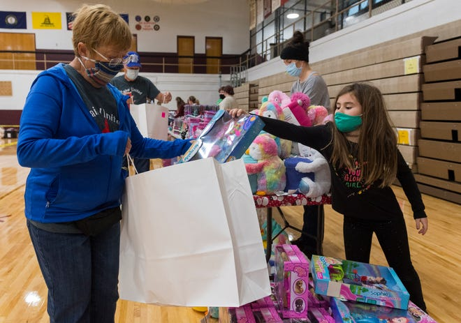 "Mary Walker holds a bag open as Eight-year-old Lyla Leavelle picks a toy for a girl during the Goodfellows ""Sack Day"" at South Middle School in Henderson, Ky., Saturday morning, Dec. 19, 2020."