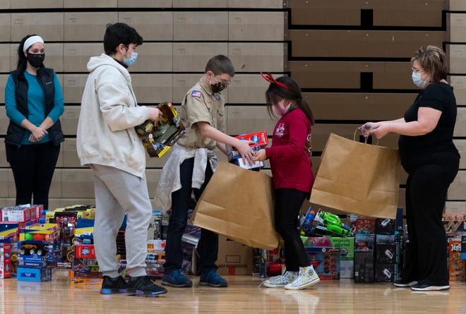 "James Murphy, left, and Christain Mayes, center, from the Boy Scout Lincoln Heritage Council Troop No. 280, load a bag with toys held by Myah Neal during the Goodfellows ""Sack Day"" at South Middle School in Henderson, Ky., Saturday morning, Dec. 19, 2020."