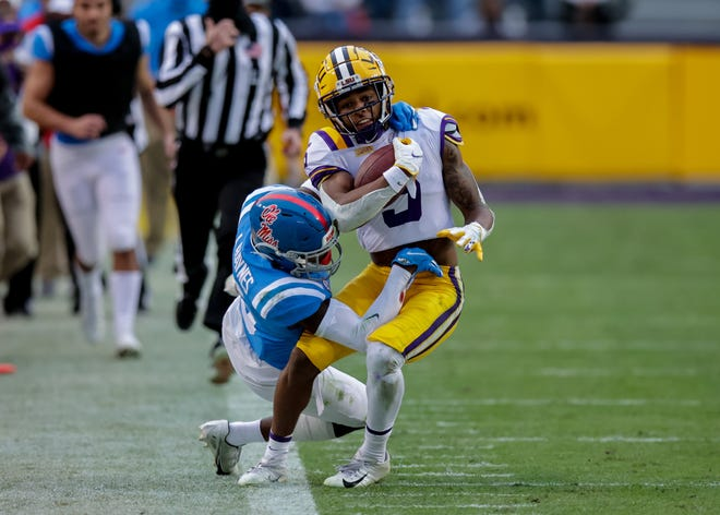 Dec 19, 2020; Baton Rouge, Louisiana, USA; LSU Tigers wide receiver Koy Moore (5) is tackled going out of bounds by Mississippi Rebels defensive back Jon Haynes (5) at Tiger Stadium. Mandatory Credit: Stephen Lew-USA TODAY Sports
