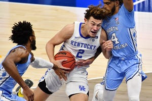 Dec 19, 2020; Cleveland, Ohio, USA; Kentucky Wildcats guard Devin Askew (2) drives to the basket between North Carolina Tar Heels guard R.J. Davis (4) and guard Leaky Black (1) during the first half at Rocket Mortgage FieldHouse.