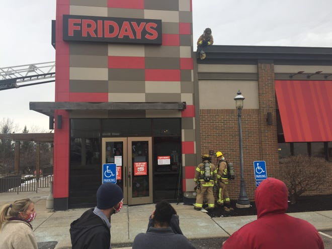 Employees at TGI Fridays watch as Springfield Township firefighters search for the origin of a fire on Saturday afternoon.