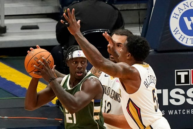 Bucks guard Jrue Holiday looks for someone to pass to while being double teamed by the Pelicans Eric Bledsoe and Steven Adams in the first half.