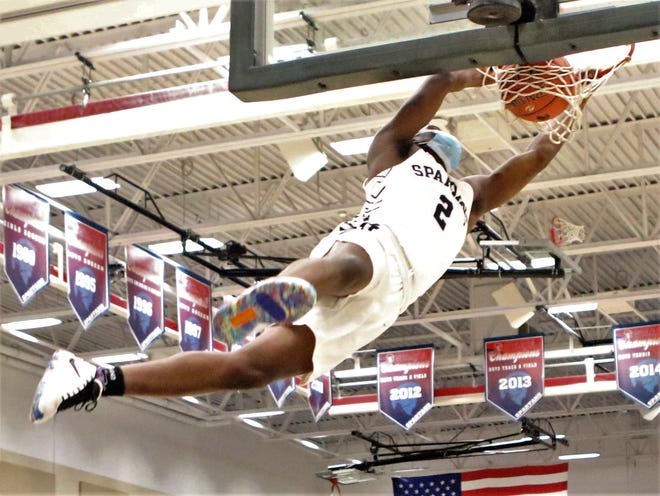 Brookfield East guard Tayshawn Bridges hangs after throwing down a dunk against Wauwatosa East.