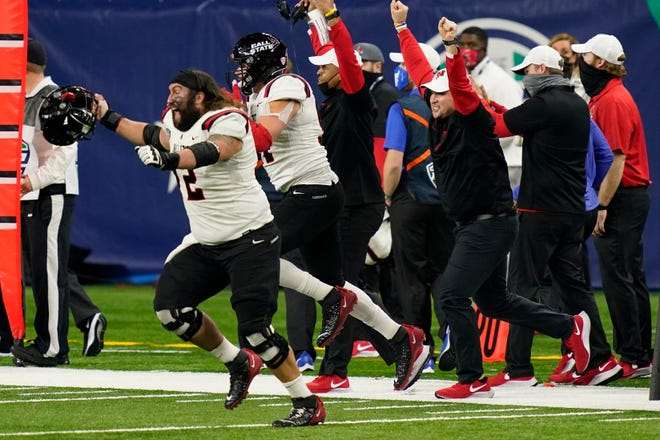 Ball State offensive lineman Anthony Todd leads players onto the field after the team defeated Buffalo in the Mid-American Conference championship NCAA college football game, Friday, Dec. 18, 2020, in Detroit. (AP Photo/Carlos Osorio)