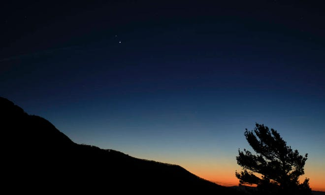 """Saturn, top, and Jupiter, below, are seen after sunset from Shenandoah National Park on Dec. 13, 2020, in Luray, Va. The two planets are drawing closer to each other in the sky as they head toward a """"great conjunction"""" on Dec. 21, when the two giant planets will appear 1/10th of 1 degree apart."""