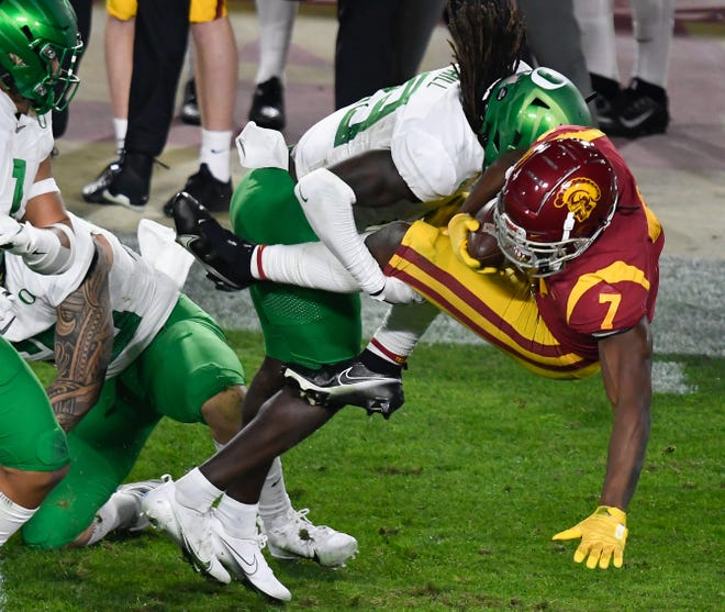 Dec 18, 2020; Los Angeles, California, USA; Oregon Ducks safety Jamal Hill (19) upends USC Trojans running back Stephen Carr (7) on a first quarter pass play at United Airlines Field at Los Angeles Memorial Coliseum. Mandatory Credit: Robert Hanashiro-USA TODAY Sports