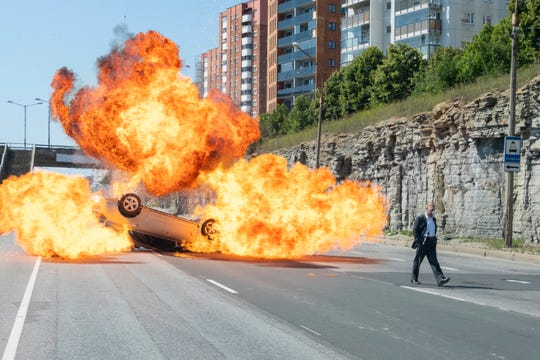 """Kenneth Branagh walks away from a car explosion in the car chase sequence from """"Tenet."""""""