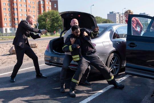 "John David Washington needs roadside assistance in an action scene from ""Tenet"" shot in Estonia."