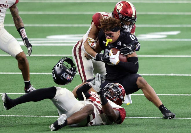 Iowa State's Xavier Hutchinson loses his helmet while being tackled by Oklahoma's Tre Norwood during the second half of Saturday's 27-21 Sooners victory in the Big 12 championship game at AT&T Stadium.