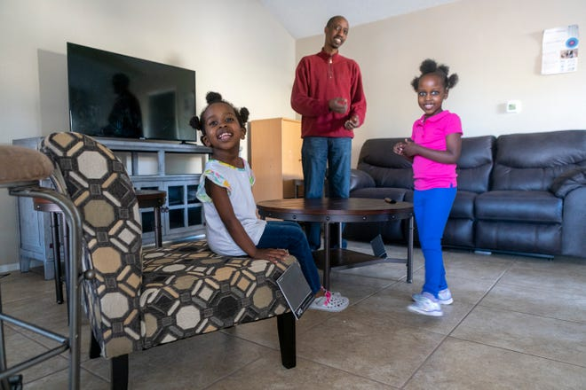 Deogratias Niyongabo and daughters Brihanna, 3, and Esther, 5, watch as their living room is filled with new furniture from Austin's Couch Potatoes. Their previous furniture was passed on to them by organizations and people who helped them after they came to the United States from Burundi in 2015.
