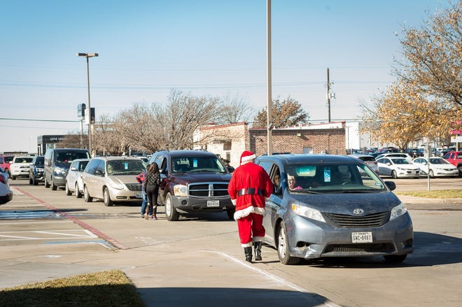 "Santa Claus visits each car during Saturday's ""Christmas after Christmas"" event, where area foster families received gifts from Dr. Rouzbeh Kordestani's office. [Shaie Williams / for the Amarillo Globe-News]"