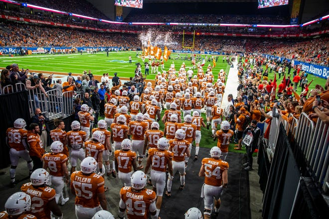The Texas Longhorns take the field before last season's Alamo Bowl win over Utah. Texas, which finished third in the Big 12 this season, will play in the Alamo Bowl again against Colorado on Dec. 29.
