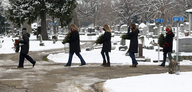 Members of the Daughters of the American Revolution carry wreaths from the mausoleum to the pavillion Saturday for the first Jane Bain National Society Daughters of the American Revolution Wreaths Across America ceremony at Alliance City Cemetery.