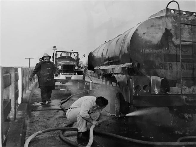 Firefighters and emergency workers struggle to put out a fire on the Sand Bar Ferry Bridge in 1962. One motorist died, and safety concerns led to the bridge being replaced.